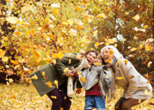 Three generations of women playing in autumn leaves