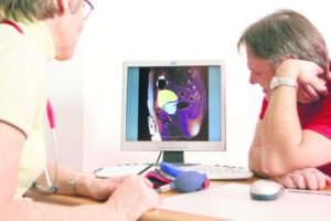 Figurants. A l'écran, IRM pelvienne. Hypertrophie prostatique modérée. Models. On screen, pelvic RMI. Moderated prostatic hypertrophy.